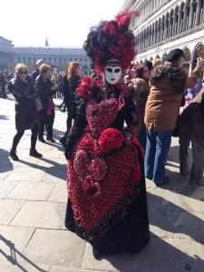 A traditional style Venetian costume with the caul/hood, full face mask and themed gown.