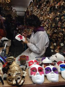 A mask-maker working in her shop.  All masks are made in the shops they are sold in.